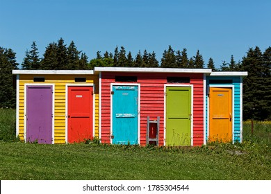 Colorful outhouses in a green field near the forest.