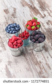 Colorful overhead fresh berries assorted arrangement  in five tin metallic cans on rustic white wooden table in studio. Blueberry, raspberry, red currant, strawberry, blackberry
