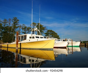 Colorful oyster boats in the water at marina.