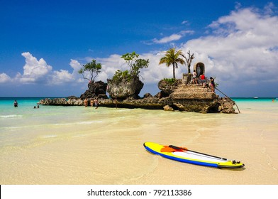 A colorful paddle boat on Boracay beach and the Christian Shrine in the background with a beautiful sky. Boracay, Phillippines.