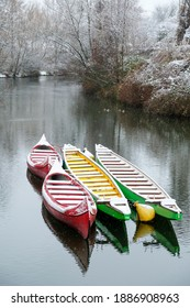 Colorful Paddle boats in hibernation on the river with snowy background and snowflakes