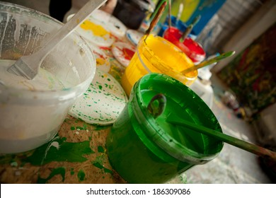 Colorful paint buckets with color spots on the table