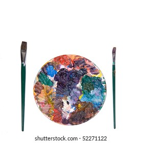 Colorful paint palette and brushes on white.