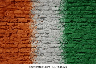 colorful painted big national flag of cote divoire on a massive old brick wall