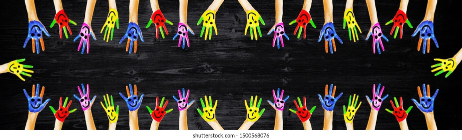 colorful painted children's hands isolated on black chalkboard