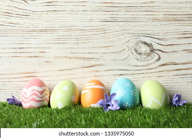 Colorful painted Easter eggs with flowers on green grass against wooden background, space for text
