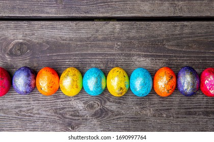 Colorful painted Easter eggs on a wooden background. Easter holiday decoration, top view.