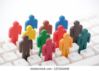 Colorful painted group of people figures on computer keyboard