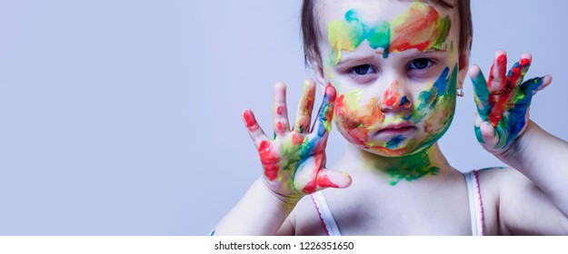 Colorful painted hands in a beautiful little child girl. Aart, childhood, color concept.