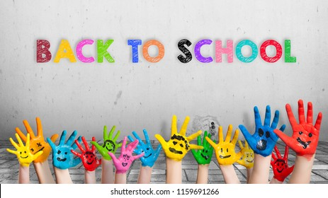 "colorful painted hands in front of a wall with the message ""back to school"""