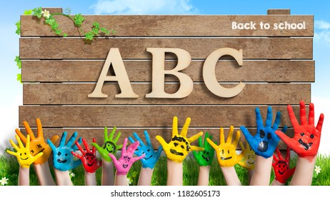 """colorful painted hands in front of a wooden sign with the letters """"ABC"""" and the message """"back to school"""""""