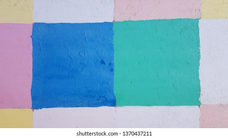 Colorful painted metal surface closeup with uneven squares of blue and green colors. Old cracked distressed structure of painted gates in Odessa city of Ukraine. Abstract background. Grunge backdrop