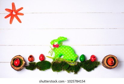 Colorful painted quail Easter eggs on white background with easter rabbit. Copy space, vintage style, top view