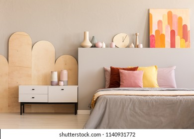 Colorful painting on grey bedhead of bed with cushions in bedroom interior with cabinet. Real photo