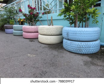 Colorful painting on the unused rubber wheel tires and using as the flower pots for flower planting