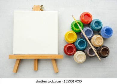 Colorful paints with paint brushes and canvas on the easels, top view.