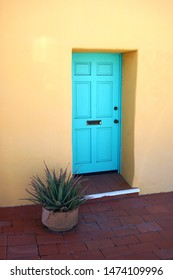 Colorful pale green door in yellow adobe wall with potted plant on brick terrace
