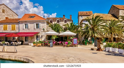 A colorful panorama of a Mediterranean resort town in summer, with restaurants and cafes along the waterfront promenade. Stari Grad, Hvar Island, Croatia. - Shutterstock ID 1212671923