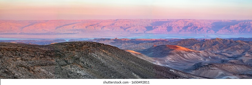 colorful panorama of the sun setting on the moav mountains in jordan and the dead sea from the negev desert hills near Arad in Israel