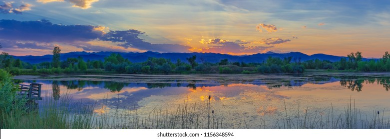 Colorful panoramic photo of a sunset behind a pond in Boulder, Colorado.