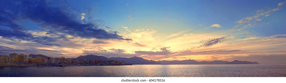 Colorful panoramic view of Sicily coastline with cloudy sunset sky, Mediterranean sea and mountains on background