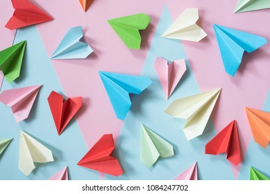 colorful paper airplanes on pastel pink and blue colored background. childhood,freedom and diversity concept