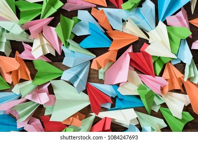 colorful paper airplanes on wooden table background. childhood,freedom,origami and diversity concept