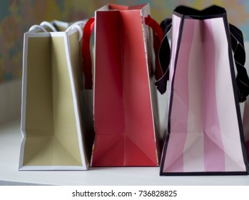 Colorful paper bags on light blurred background
