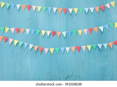 Colorful paper bunting on rustic wooden background