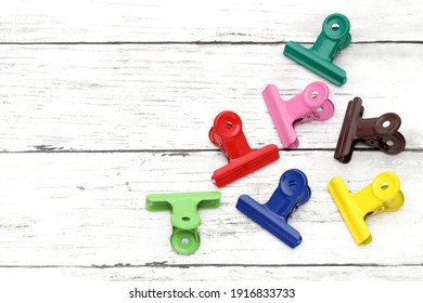 Colorful paper clips on white grunge wooden table