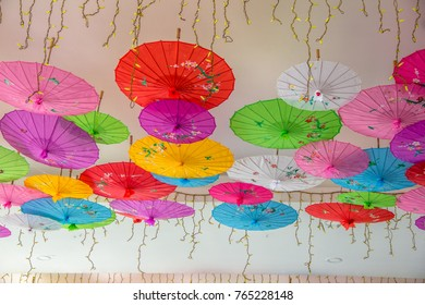 Colorful paper cocktail umbrellas hanging on wall