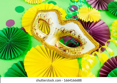 Colorful paper confetti, carnivale mask and colored serpentine on a green background with copy space, greeting card and party invitation template design for carnival or birthday, Mardi Gras,