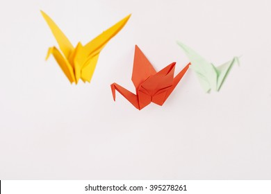 Colorful paper cranes (origami) on a white background.