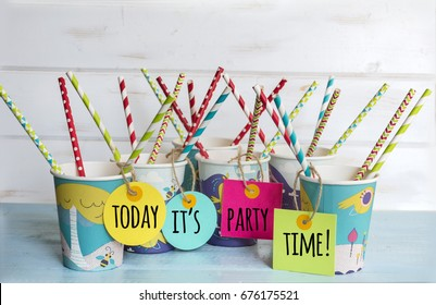 Colorful paper cups with  straws  and today it's party time message.Party time concept