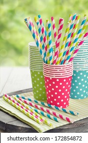Colorful paper cups and striped straws for birthday party.