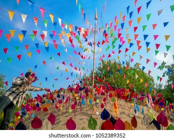 Colorful paper flag in the temple sand heap in Songkran festival(Thai New Year) with Soft light in bright day blue sky background culture northeastern  udonthani  in Thailand.