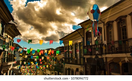 """Colorful paper flags and balloons decorrating street in Brazil. Traditional habit during june party, or """"festas juninas"""" in portuguese. On background, cloud sky, mountains and trees."""