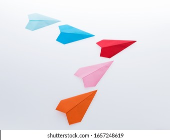 Colorful paper planes on white background.