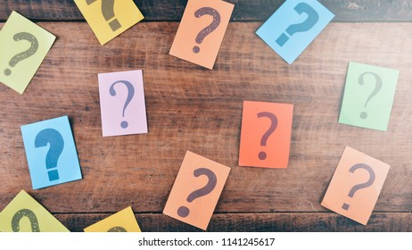 colorful paper with QUESTION MARK on wooden table. FAQ, questions and brainstorming concept