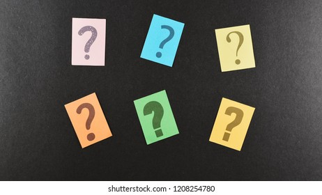 colorful paper with QUESTION MARK over dark background. FAQ, questions and brainstorming concept
