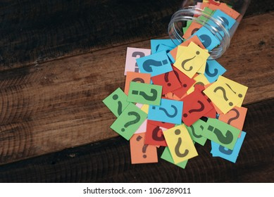 colorful paper with question mark in a plastic jar on wooden table. questions and diversity concept. FAQ and Q&A background concept