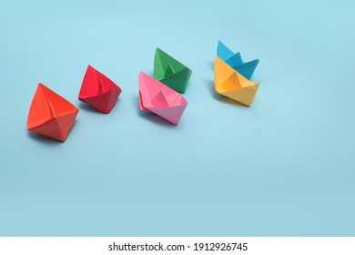 Colorful paper ships on white background, Leadership and Business competition concepts