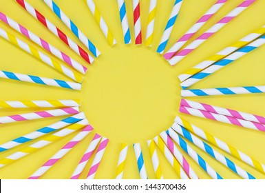 Colorful paper straws in a circle on a yellow background, with copy space. Summer sun flat lay concept.