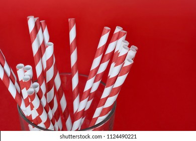 Colorful paper straws with copyspace on red background