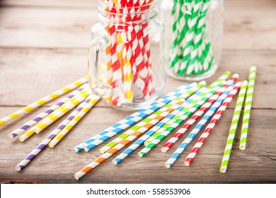 Colorful paper straws on wooden background. Event and party supplies. Selective focus. Copy space