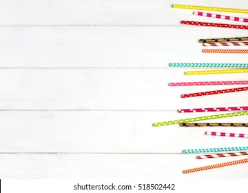 Colorful paper straws for party on the wooden background. Top view.