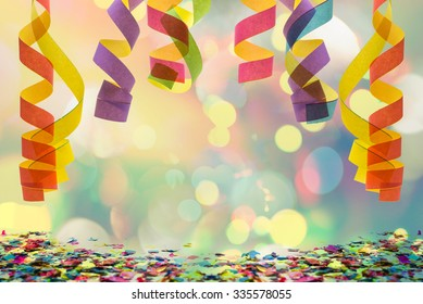 colorful paper streamer hanging from top with confetti on the bottom for celebration