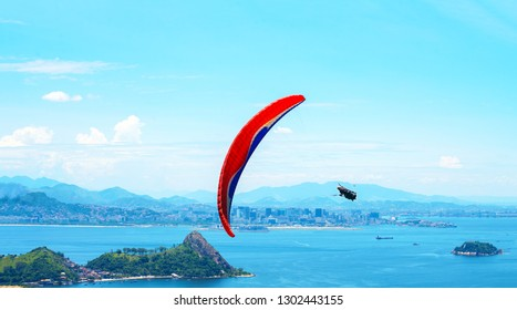 A colorful parachute with skydiver on sunny blue sky background. Active lifestyle. Extreme sport. Concept of holidays, vacation, tourism. horizontal. Aerial view of Rio de Janeiro with turquoise water