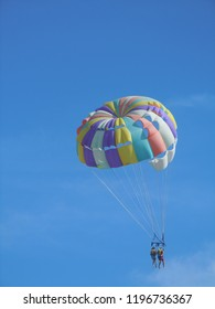 Colorful parachute with two people against the blue sky.