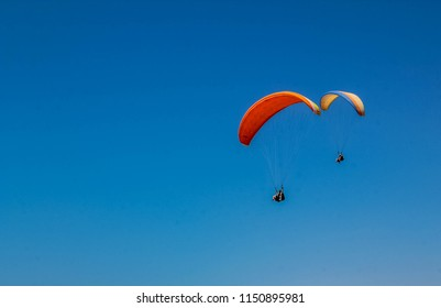 Colorful paragliders in blue sky